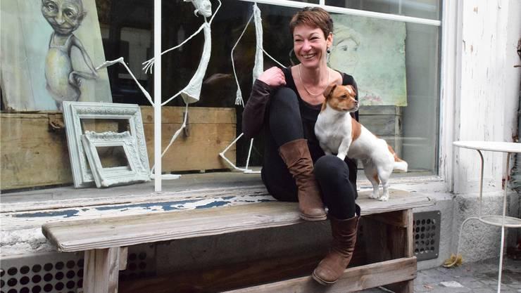 Das Gemälde am linken Bildrand zeigt eine der Figuren aus Simone Meiers Fantasie, doch auch reale Motive zeichnet die Künstlerin – den kleinen Hund auf ihrem Schoss gibts ebenfalls auf Grusskarte. Nora Güdemann