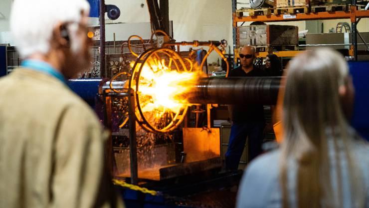 Andreas Loosli zeigt an der Industrienacht bei der Härterei Gerster AG den Besucherinnen und Besuchern, wie er an der Flammhärteanlage eine Walze zum Härten über 900 Grad Celsius erwärmt.