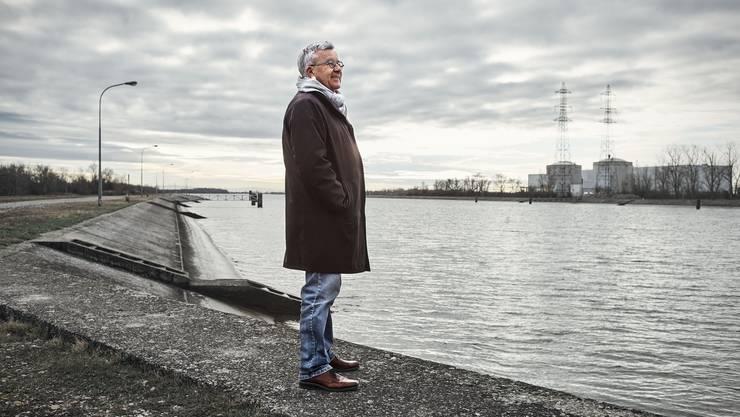 Blick auf das Monstrum: Ruedi Rechsteiner auf der künstlichen Rheininsel. Das AKW Fessenheim im Hintergrund wird nach langjähriger Kontroverse dieses Jahr endgültig abgeschalten.