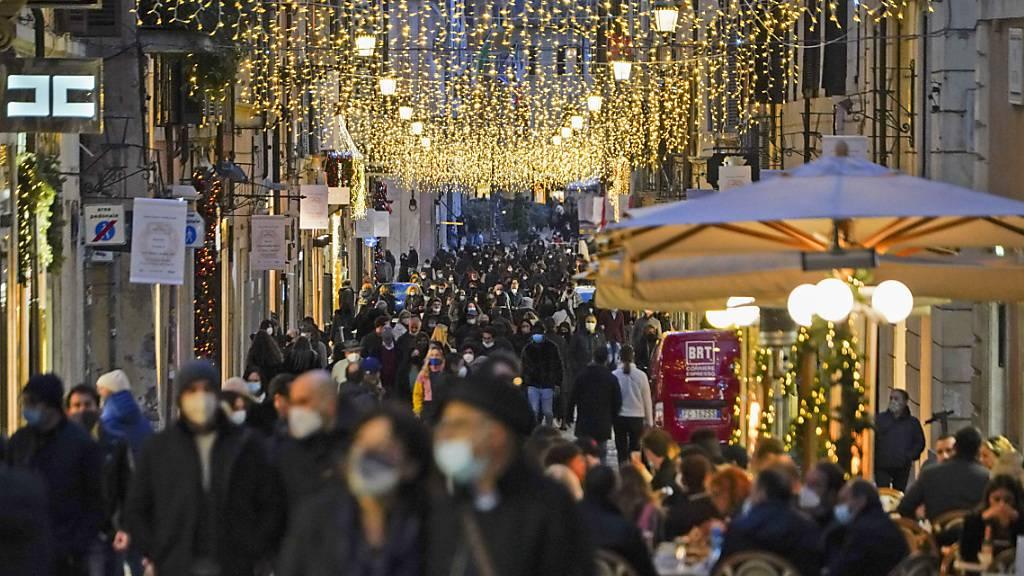 Zahlreiche Menschen mit Mund-Nasen-Schutz gehen eine weihnachtlich geschmückte Einkaufsstraße in der Innenstadt entlang. Foto: Andrew Medichini/AP/dpa