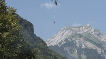 Ein Helikopter transportiert Löschwasser zum Absturzort am Lopper in Hergiswil NW. (Archivbild)