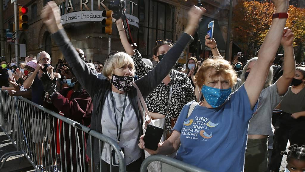 Menschen mit Mund-Nasen-Schutz feiern vor dem Pennsylvania Convention Center, nachdem der demokratische Präsidentschaftskandidat Joe Biden zum Sieger erklärt wurde. Foto: Rebecca Blackwell/AP/dpa