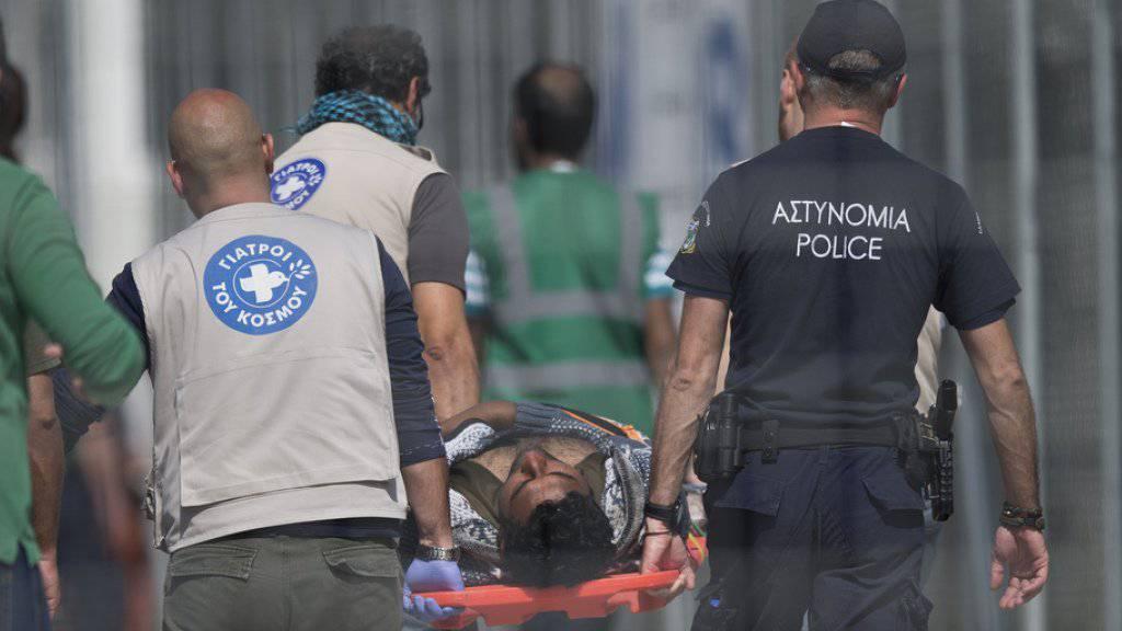 Mitglieder der Polizei und der Hilfsorganisation Ärzte der Welt tragen einen Pakistaner auf einer Bahre. Rund 70 pakistanische Flüchtlinge im Lager Moria auf der griechischen Insel Lesbos befinden sich im Hungerstreik.