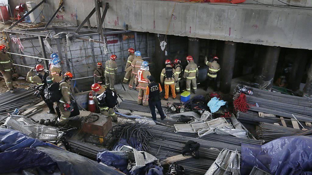 Rettungskräfte suchen nach Verschütteten nach einer Explosion in einer U-Bahn-Baustelle in Südkorea.