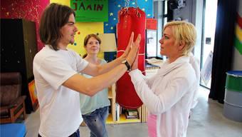 Jugendarbeiter Sebastian Illing macht mit Jasmin Hilty (rechts) und Lena Keller vom Ferienpass-Team eine Startübung von «Kampfesspiele».ROB