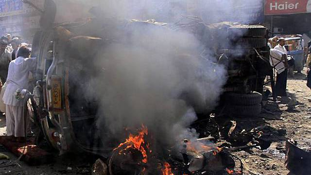 Leute stehen um brennendes Autowrack