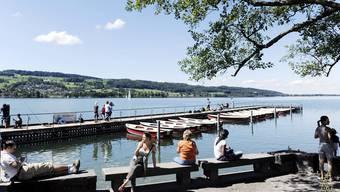Geniessen das schöne Wetter: Passanten auf dem Ufer des Greifensees. (Archivbild)