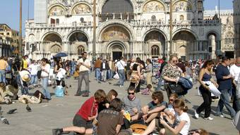 Touristen auf dem Markusplatz in Venedig. Ab Mitte nächsten Jahres müssen Tagestouristen Eintrittsgeld für einen Besuch in der Lagunenstadt bezahlen. (Archivbild)