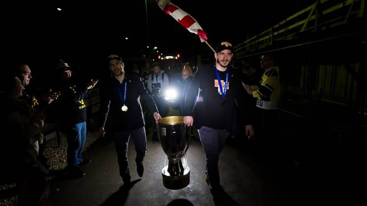 Philip-Michael Devos (l.) und Jordane Hauert tragen die Cup-Trophäe ins Stadion in Pruntrut.