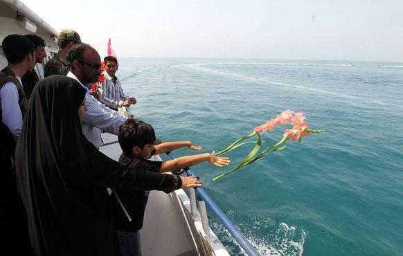 Trauernde Angehörige werfen Blumen in den Persischen Golf.