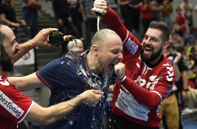 Trainer Zoltan Majeri (M.) erhält von Nemanja Sudzum (l.) und Leonard Pejkovic die obligate Champagnerdusche.
