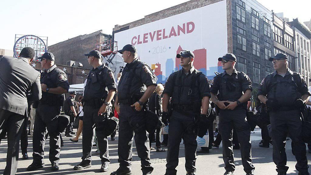 Polizisten sichern den Parteitag der US-Republikaner in Cleveland. Sie nahmen 17 Demonstranten fest, nachdem eine US-Fahne in Brand gesetzt worden war und die Flammen auf Protestierende übergriff.