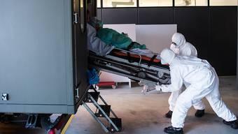 Das Tessin ist landesweit am stärksten vom Coronavirus betroffen: Soldaten der Schweizer Armee beim Transport eines Patienten mit Covid-19 am Eingang der Notaufnahme im Kantonsspital ''La Carita'' in Locarno.