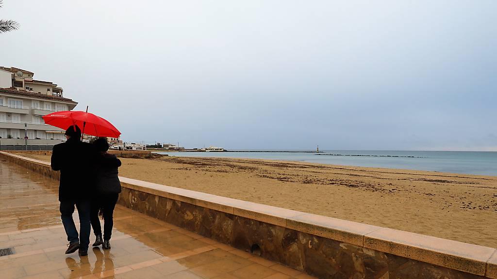 Ein Paar spaziert mit einem Regenschirm am Strand von Palma entlang. Foto: Clara Margais/dpa