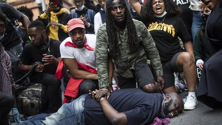 Demonstranten stellen in New York die Szene nach, die zum Tod von George Floyd führte. Der Protest der Demonstranten richtet sich gegen Rassismus und Polizeigewalt. Foto: Wong Maye-E/AP/dpa