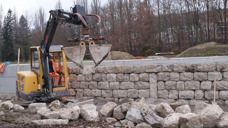 Die Betonmauer beim Reitplatz wird mit Steinen verkleidet