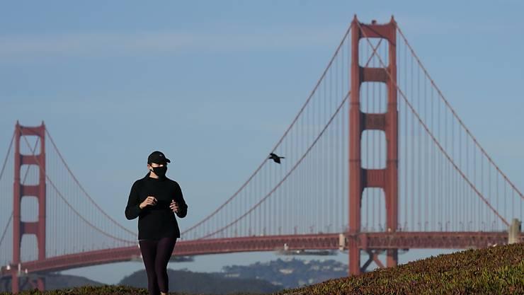 Eine Frau mit Mund-Nasen-Schutz joggt unweit der Golden Gate Bridge in San Francisco. In fünf Bezirken in der Region sind die Bewohner dazu angehalten, ihr Zuhause nicht zu verlassen. Foto: Jeff Chiu/AP/dpa