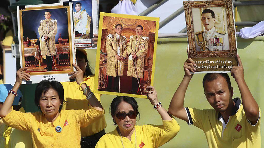 Lang lebe der König: Monarchisten in gelben Hemden halten Porträts ihrer neuen Königs in die Luft.
