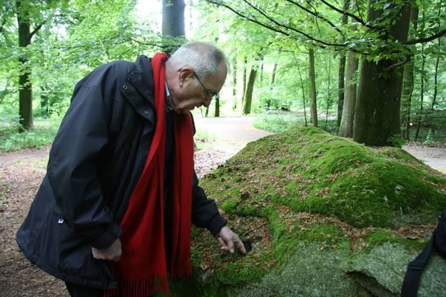 Benjamin Faessler zeigt an der zweiten Station Bearbeitungsspuren im Findling