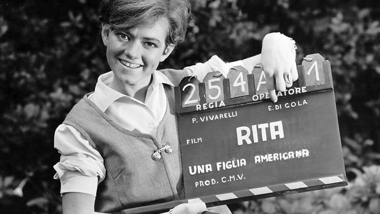 """Rita Pavone posiert 1965 in Rom mit der Klappe des Films """"Rita - una figlia americana"""", an dem sie mitwirkte."""