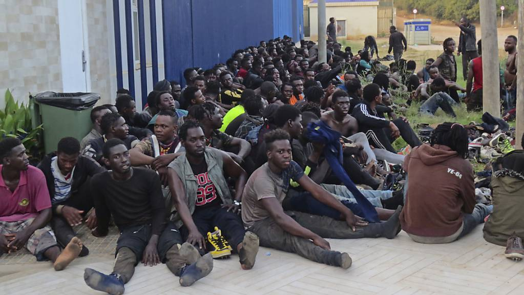 Eine Gruppe von Migranten sitzt in einem Aufnahmezentrum in Melilla. Insgesamt 238 Menschen sind am frühen Donnerstagmorgen über den Grenzzaun zwischen Marokko und Spanien gesprungen. Dabei seien laut Angaben des TV-Senders RTVE drei spanische Polizisten und 18 Migranten verletzt worden. Foto: Uncredited/Europa Press/dpa