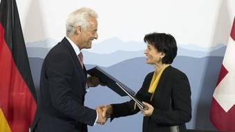 Bundesrätin Doris Leuthard und der deutsche Verkehrsminister Peter Ramsauer tauschen die unterzeichneten Dokumente aus