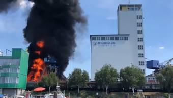 Im Basler Rheinhafen fing am Freitagnachmittag ein Altholzlager Feuer. Die Polizei warnte die Bevölkerung.