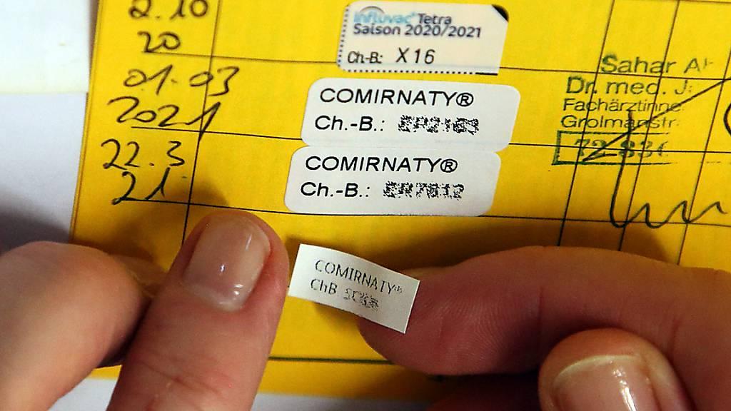 Eine Ärztin klebt den Nachweis für die dritte Impfung mit dem Comirnaty-Impfstoff des Herstellers Biontech/Pfizer in ein Impfbuch. Menschen mit geschwächtem Immunsystem sollen laut einem internationalen Expertengremium der WHO eine dritte Dosis des Corona-Impfstoffs erhalten. Foto: Wolfgang Kumm/dpa - ACHTUNG: Chargennummern wurden aus rechtlichen Gründen gepixelt