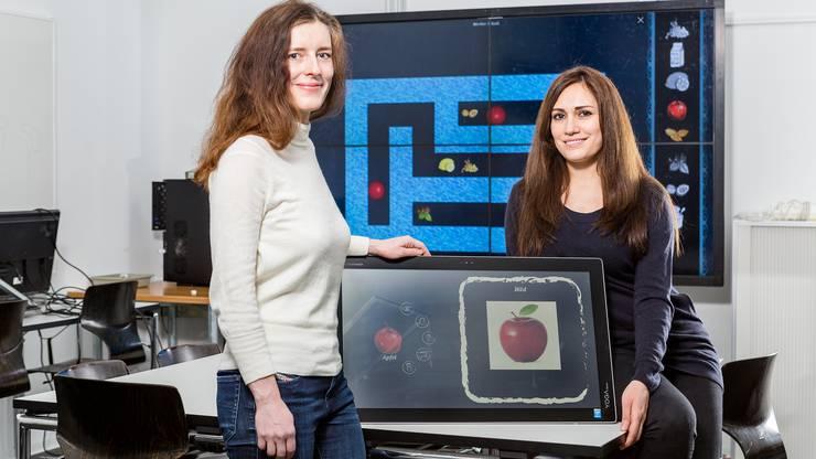 Viviane Bendjus (links) und Souzan Alhenawi präsentieren auf dem Tablet ihr Spiel, in dem es darum geht, Zutaten für ein Kochrezept zu sammeln.