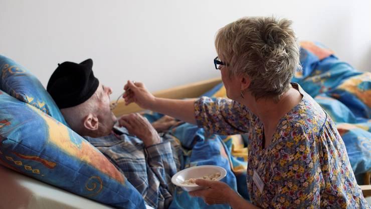 Im Hemd und mit einem Béret auf dem Kopf: Frühstück im Bett mit Herrn K. und seiner Pflegerin Marianne Müller.
