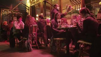 Menschen sitzen an Tischen auf einer Caféterrasse in Paris. Erneut gibt es Einschränkungen bei den Öffnungszeiten von Bars und Restaurants. Foto: Lewis Joly/AP/dpa