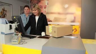 Die ehemalige Poststellenleiterin Sonja Schmidiger (links) erklärt AXA-Mitarbeiterin Ines Ruch das Postgeschäft.