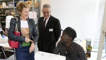Bundesrätin Simonetta Sommaruga letztes Jahr am Besuchstag des Bundesasylzentrums Boudry. Asylsuchenden sollte auch dann Beschäftigung und Ausbildung - wie hier Nähen - geboten werden, wenn sie bereits abgewiesen sind, empfiehlt die Eidgenössische Migrationskommission EKM. (Archivbild)