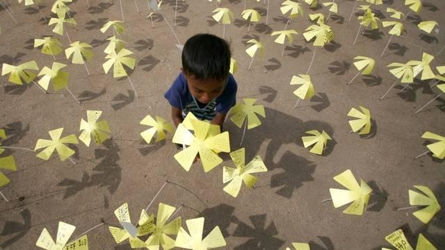 In Indonesien wird der Opfer der Tsunami-Katastrophe vor sechs Jahren gedacht - ein Junge pflanzt eine Papierblume voller Wünsche