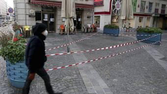 Ein Mann mit Mund-Nasen-Schutz geht an einem geschlossenen Cafe in der Wiener Innenstadt vorbei. Foto: Ronald Zak/AP/dpa