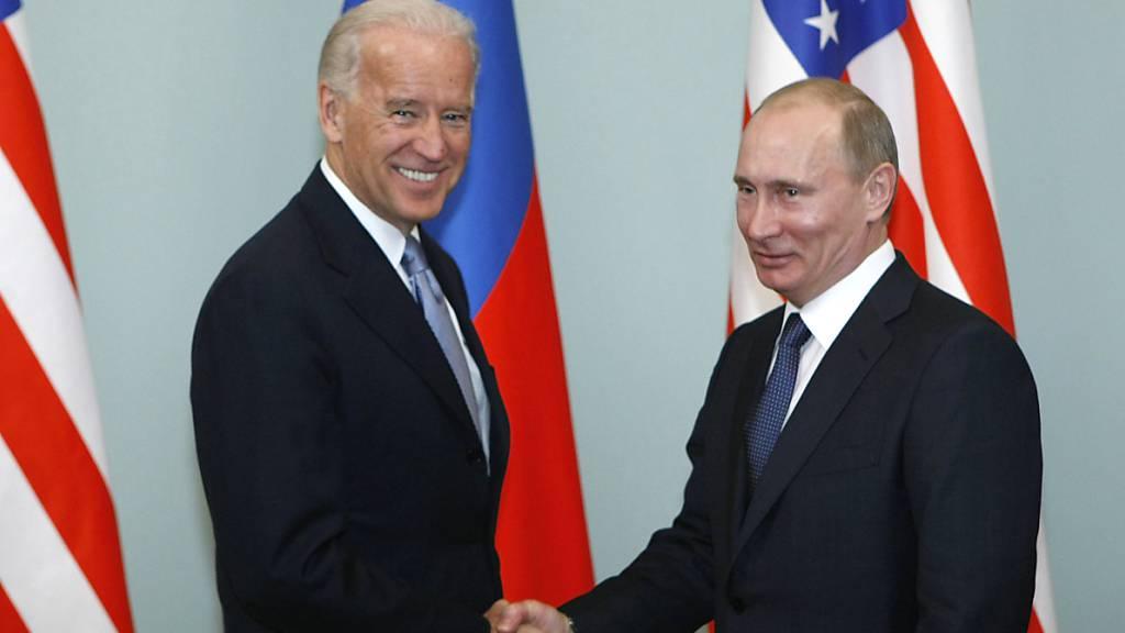 ARCHIV - Joe Biden (l), damaliger Vizepräsident der USA, gibt Wladimir Putin, Präsident von Russland, die Hand. Foto: Alexander Zemlianichenko/AP/dpa