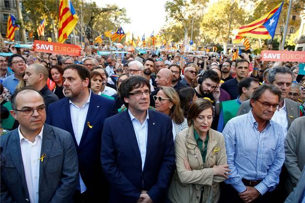 Der Präsident der katalanischen Regionalregierung, Carles Puigdemont (Mitte) nimmt zusammen mit Kollegen der der entmachteten Regionalregierung an einem Protestmarsch in Barcelona teil. Keystone