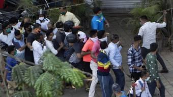 Massenansturm auf die Schnapsläden: Ein Polizist schlägt in Mimbai auf Kunden ein, welche die Abstandsregeln nicht einhalten.