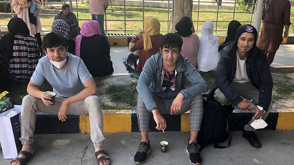 Männer sitzen vor dem Flughafen. 27 abgeschobene Männer kamen mit der 40. Sammelabschiebung seit dem ersten derartigen Flug im Dezember 2016 in der afghanischen Hauptstadt an. Damit haben Bund und Länder bisher 1104 Männer nach Afghanistan zurückgebracht. Foto: Qiamuddin Noori/dpa