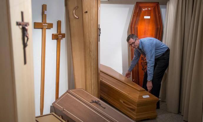 Rolf Arnold vom Luzerner Bestattungsunternehmen Arnold und Sohn bei der Arbeit mit einem Sarg.