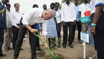 Bundespräsident Alain Berset pflanzt bei seinem Besuch im Flüchtlingslager Kakuma in Kenia einen Baum.