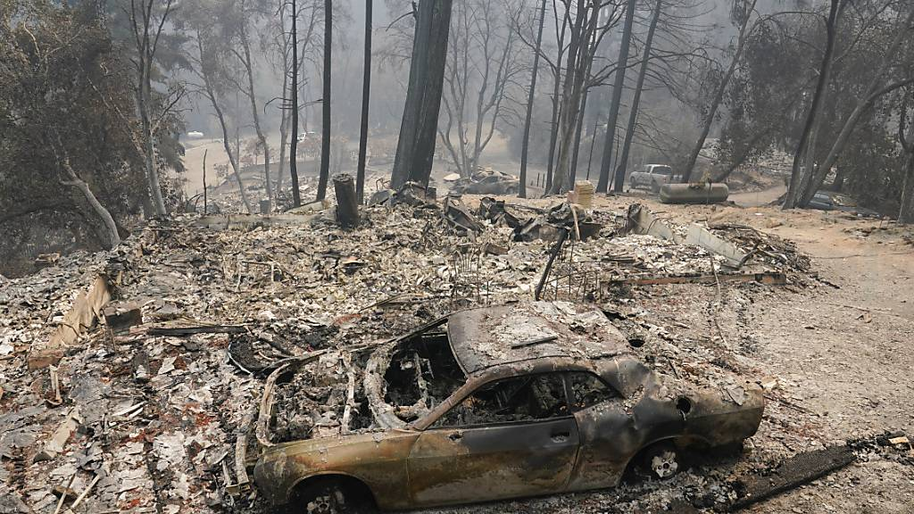 Ein ausgebranntes Auto steht in der Nähe eines Waldes. Etwas kühlere Temperaturen nach einer Hitzewelle haben die Löscharbeiten der US-Feuerwehr bei den Waldbränden in Kalifornien begünstigt. Foto: Marcio Jose Sanchez/AP/dpa