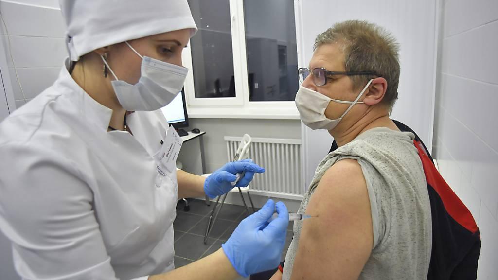 Eine medizinische Mitarbeiterin verabreicht einem Mann den Corona-Impfstoff Sputnik V. Foto: Sergey Kiselev/Moscow News Agency/AP/dpa