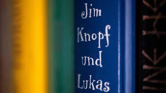 """Das Kinderbuch «Jim Knopf und Lukas der Lokomotivführer» des Autors Michael Ende steht in einem Bücherregal. (zu dpa """"Rassismus in Lummerland? Die Causa Jim Knopf"""") Foto: Marijan Murat/dpa"""