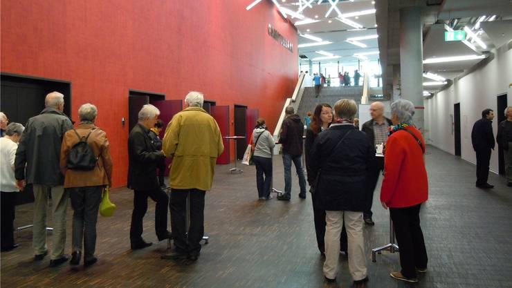 Die Treppe führt hinunter zum roten Campussaal, der sich als Publikumsmagnet entpuppt. Am Tischchen hat sich eine kleine Diskussionsrunde versammelt.