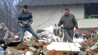 Eine Familie aus Petrinja sucht in den Trümmern ihres Hauses nach Habseligkeiten.