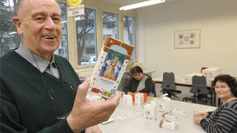 René Meier hält die Kinderschokolade in den Händen, die Mitarbeiterinnen einpacken. Nicole Nars-Zimmer
