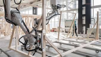 Zwei Roboter arbeiten beim Zusammenbau des Holzmoduls zusammen. Ihr Bewegungspfad wird laufend anhand des Baufortschritts berechnet.