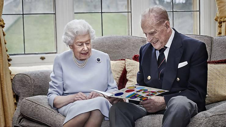 Das Foto zeigt Elizabeth und Philip, die eine selbstgemachte Karte zum 73. Hochzeitstag betrachten, die ihnen zuvor von ihren Urenkeln überreicht wurde.