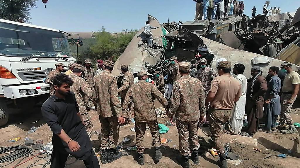 HANDOUT - Truppen der pakistanischen Armee und Rettungskräfte sind am Ort der Zugkollision im Einsatz. Foto: Uncredited/Inter Services Public Relations/AP/dpa - ACHTUNG: Nur zur redaktionellen Verwendung im Zusammenhang mit der aktuellen Berichterstattung und nur mit vollständiger Nennung des vorstehenden Credits